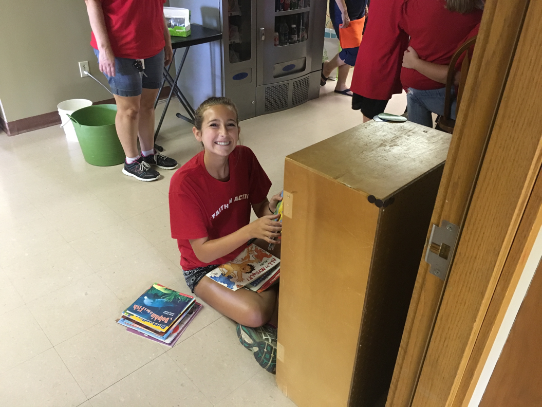 A student helps clean a book shelf at a local Children's First building.